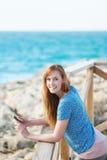 Mujer con su móvil en la playa Imagen de archivo