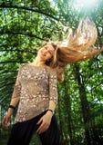 Mujer con su pelo rubio agradable en el aire Foto de archivo libre de regalías