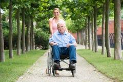Mujer con su viejo padre mayor On Wheelchair foto de archivo libre de regalías