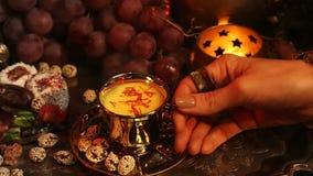 Mujer con té de consumición y la consumición de la joyería oriental de los dulces marroquíes tradicionales Taza de té de la leche