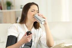 Mujer con tensión arterial baja que bebe soda dulce Imagen de archivo libre de regalías