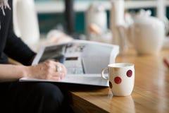 Mujer con un anillo agradable grande que lee una revista y que bebe té en una tabla de madera fotos de archivo