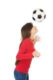 Mujer con un balón de fútbol en la cabeza Imágenes de archivo libres de regalías