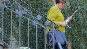 Mujer con un bolso que viene abajo las escaleras metrajes