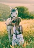 Mujer con un caballo en un prado Imagen de archivo