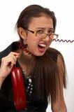 Mujer con un cable del teléfono Imagenes de archivo