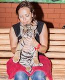 Mujer con un cachorro de tigre en su revestimiento imagen de archivo