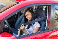 Mujer con un cinturón de seguridad en un coche Fotos de archivo