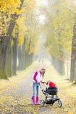 Mujer con un cochecito de niño Fotos de archivo libres de regalías
