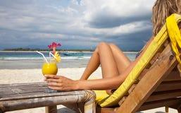 Mujer con un coctel en la playa Imágenes de archivo libres de regalías