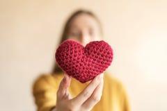 Mujer con un corazón hecho a ganchillo rojo Fotografía de archivo