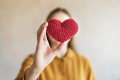 Mujer con un corazón hecho a ganchillo rojo Imágenes de archivo libres de regalías