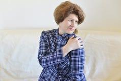 mujer con un dolor agudo en su hombro Imagen de archivo libre de regalías