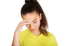Mujer con un dolor de cabeza que lleva a cabo la pista Foto de archivo libre de regalías