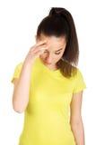 Mujer con un dolor de cabeza que lleva a cabo la pista Fotografía de archivo libre de regalías