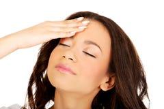 Mujer con un dolor de cabeza que lleva a cabo la pista Foto de archivo