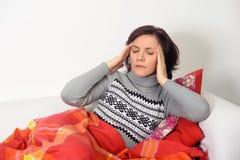 Mujer con un dolor de cabeza que se sienta en el sofá Imagenes de archivo
