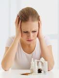 Mujer con un dolor de cabeza y una gripe y con las medicinas Foto de archivo libre de regalías