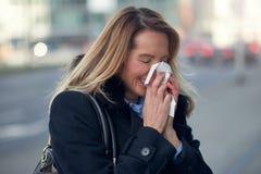 Mujer con un frío estacional del invierno que sopla su nariz Foto de archivo