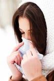 Mujer con un frío que sostiene un tejido Fotografía de archivo