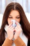 Mujer con un frío que sostiene un tejido Imagenes de archivo