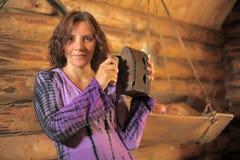 Mujer con un hierro viejo Imagenes de archivo