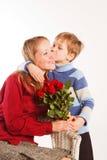 Mujer con un hijo y con el ramo de rosas rojas Foto de archivo libre de regalías