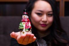 Mujer con un juguete del muñeco de nieve Fotografía de archivo libre de regalías