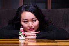 Mujer con un juguete del muñeco de nieve Imagen de archivo
