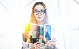 Mujer con un libro en una oficina Fotografía de archivo libre de regalías