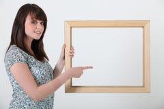 Mujer con un marco Imagen de archivo