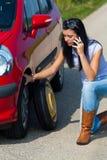 Mujer con un neumático plano en coche Imagenes de archivo