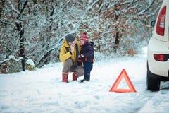 Mujer con un niño en el camino del invierno foto de archivo