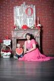 Mujer con un niño por la chimenea Imagen de archivo