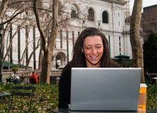Mujer con un ordenador en un parque Imagen de archivo
