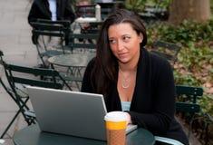 Mujer con un ordenador en un parque Imagen de archivo libre de regalías