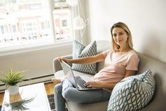 Mujer con un ordenador portátil en el sofá en casa foto de archivo