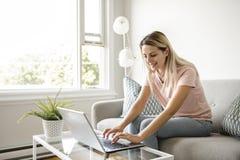 Mujer con un ordenador portátil en el sofá en casa fotos de archivo libres de regalías
