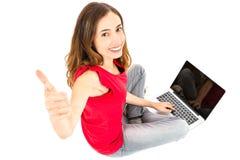 Mujer con un ordenador portátil que da los pulgares para arriba Fotografía de archivo