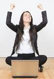 Mujer con un ordenador portátil que se sienta en el piso Foto de archivo