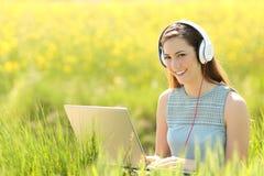 Mujer con un ordenador portátil y los auriculares en un campo Fotografía de archivo