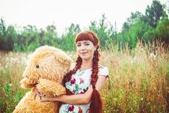 Mujer con un oso de peluche en naturaleza Imagenes de archivo