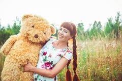 Mujer con un oso de peluche en naturaleza Foto de archivo