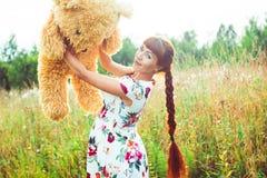 Mujer con un oso de peluche en naturaleza Fotos de archivo