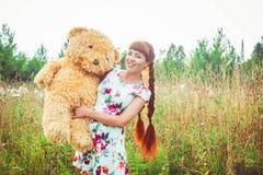 Mujer con un oso de peluche en naturaleza Imagen de archivo libre de regalías