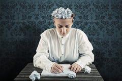 Mujer con un papel arrugado en top de su cabeza y escritura en el papel Fotografía de archivo libre de regalías