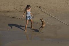 Mujer con un perro en la playa arenosa de Sitges Imagen de archivo