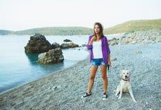 Mujer con un perro en un paseo en la playa Imagen de archivo libre de regalías