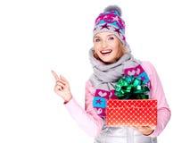Mujer con un regalo en una prendas de vestir exteriores del invierno que señala por el finger Imagenes de archivo