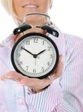 Mujer con un reloj de alarma en una mano. Imagenes de archivo